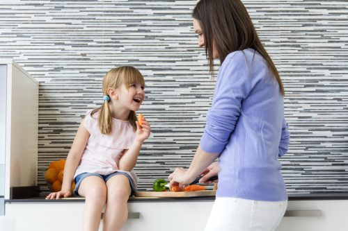 Portrait of  young woman and little girl eating carrots in the kitchen