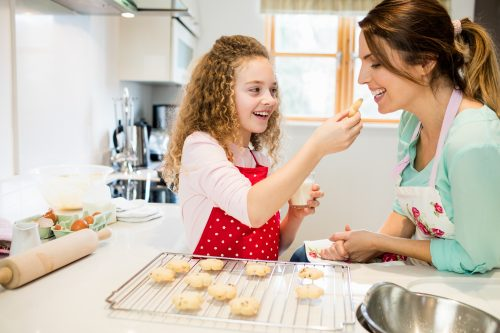 Daughter feeding cookies to her mother in kitchen