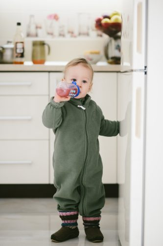 Little boy in green sweater drinks from a spotted bottle standing on white kitchen